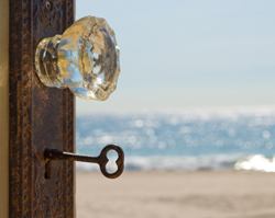 A key in a door - in the door frame - the ocean on a sunny day