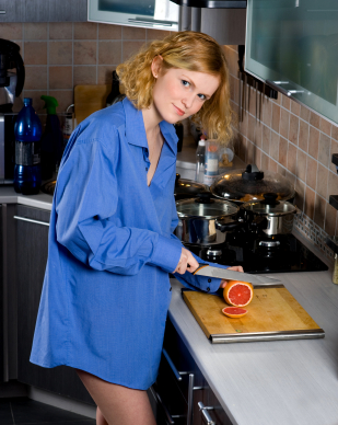 Redhead girl dressed in blue mens shirt cutting orange in kitchen
