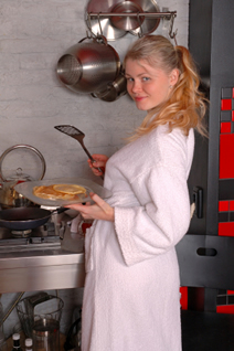 Redhead young girl, dressed in bathrobe, making pancakes